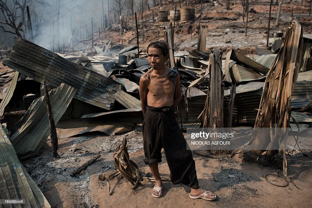 A Myanmar refugee smoke his pipe as he looks at rescue workers while standing amongst his burnt out camp at the Mae Surin camp in Mae Hong Son province on March 23, 2013. The toll from a blaze that swept through a camp in northern Thailand has risen to 45, authorities said, after hundreds of shelters for refugees from Myanmar were reduced to ashes. Over 100 people were injured in the fire, which destroyed about 400 homes at the Mae Surin camp in Mae Hong Son province, Thailand's Interior Ministry said as it updated the death toll. AFP PHOTO / Nicolas ASFOURI
