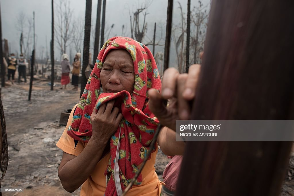 Myanmar refugee Thaku, 65, who is the only survivor of a family of five, looks from a distance where the bodies of her family are inspected by arsenic police for DNA samples at the Mae Surin camp in Mae Hong Son province on March 24, 2013. Thai rescue workers picked through the ashes of hundreds of shelters for Myanmar refugees, after a ferocious blaze swept through a camp in northern Thailand killing 35 people. AFP PHOTO/ Nicolas ASFOURI