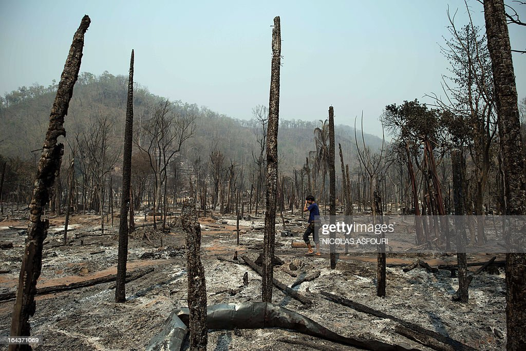 A Myanmar refugee walks among burnt houses at the Mae Surin camp in Mae Hong Son province, on March 23, 2013. The toll from a blaze that swept through a camp in northern Thailand has risen to 45, authorities said, after hundreds of shelters for refugees from Myanmar were reduced to ashes. Over 100 people were injured in the fire, which destroyed about 400 homes at the Mae Surin camp in Mae Hong Son province, Thailand's Interior Ministry said as it updated the death toll. AFP PHOTO/ Nicolas ASFOURI