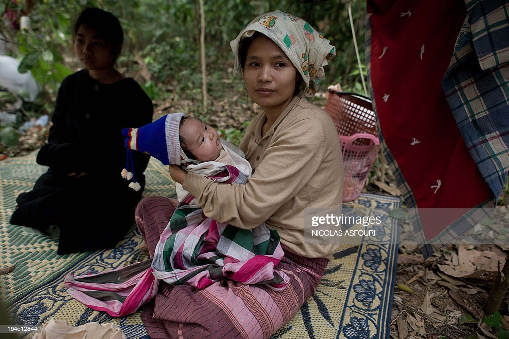 A Myanmar refugee watches rescue workers as she holds her new born baby in the early morning at the Mae Surin camp in Mae Hong Son province on March 24, 2013. Thai rescue workers picked through the ashes of hundreds of shelters for Myanmar refugees, after a ferocious blaze swept through a camp in northern Thailand killing 35 people. Around 100 people were injured in Friday's fire at the Mae Surin camp in Mae Hong Son province, provincial governor Narumol Paravat told AFP by telephone, giving a reduced toll from the 45 dead previously stated. AFP PHOTO/ Nicolas ASFOURI