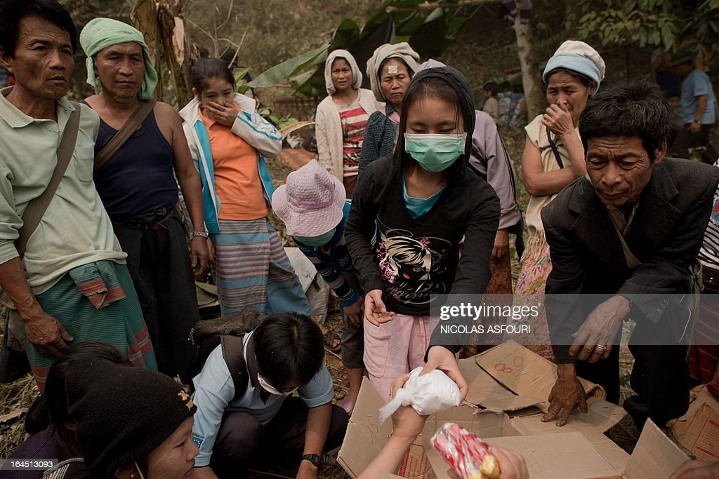 Myanmar refugees receive goods relief aid and food at the Mae Surin camp in Mae Hong Son province on March 24, 2013. Thai rescue workers picked through the ashes of hundreds of shelters for Myanmar refugees, after a ferocious blaze swept through a camp in northern Thailand killing 35 people. Around 100 people were injured in Friday's fire at the Mae Surin camp in Mae Hong Son province, provincial governor Narumol Paravat told AFP by telephone, giving a reduced toll from the 45 dead previously stated. AFP PHOTO/ Nicolas ASFOURI