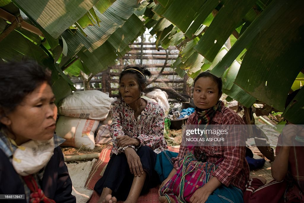 Myanmar refugees sit inside a temporary shack made of leafs in the early morning at the Mae Surin camp in Mae Hong Son province on March 24, 2013. Thai rescue workers picked through the ashes of hundreds of shelters for Myanmar refugees, after a ferocious blaze swept through a camp in northern Thailand killing 35 people. Around 100 people were injured in Friday's fire at the Mae Surin camp in Mae Hong Son province, provincial governor Narumol Paravat told AFP by telephone, giving a reduced toll from the 45 dead previously stated. AFP PHOTO/ Nicolas ASFOURI