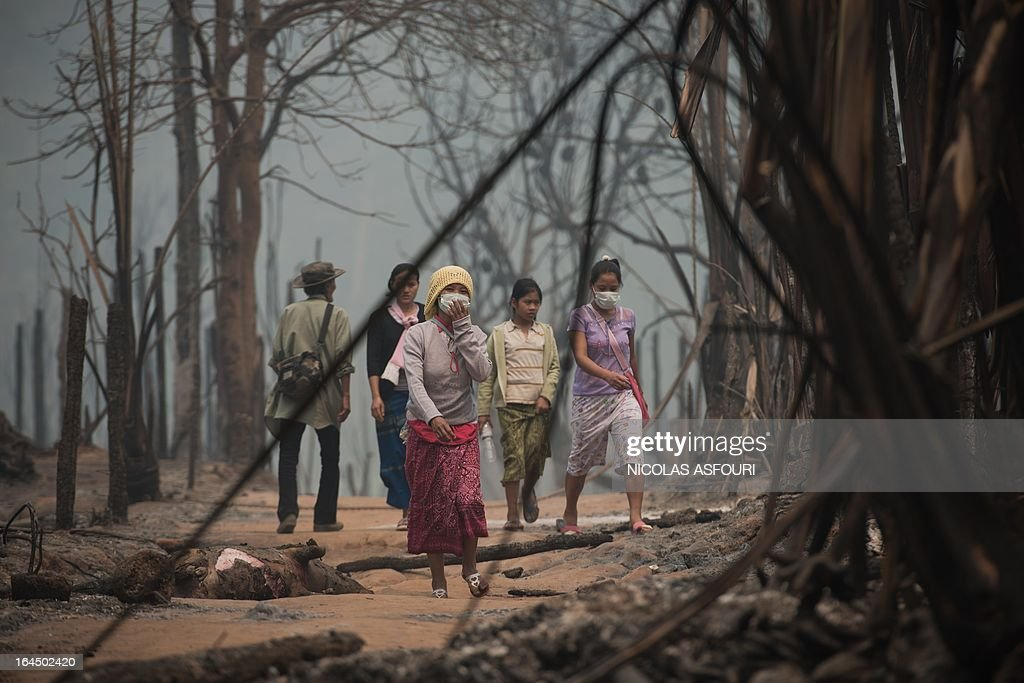 Myanmar refugees walk through their destroyed camp, at the Mae Surin camp in Mae Hong Son province on March 24, 2013, after around 100 people were injured a fire on March 22. Thai rescue workers picked through the ashes of hundreds of shelters for Myanmar refugees on March 23 after a ferocious blaze swept through a camp in northern Thailand killing 35 people. AFP PHOTO/ Nicolas ASFOURI