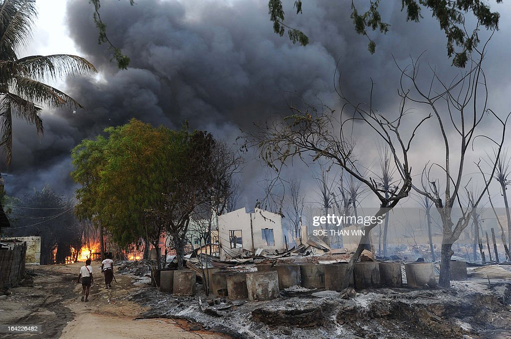 Myanmar residents walk past destroyed houses as black smoke rises from burning buildings in riot-hit Meiktila, central Myanmar on March 21, 2013. At least 10 people have been killed in riots in central Myanmar, an MP said, prompting international concern at the country's worst communal unrest since a wave of Buddhist-Muslim clashes last year. AFP PHOTO/ Soe Than WIN