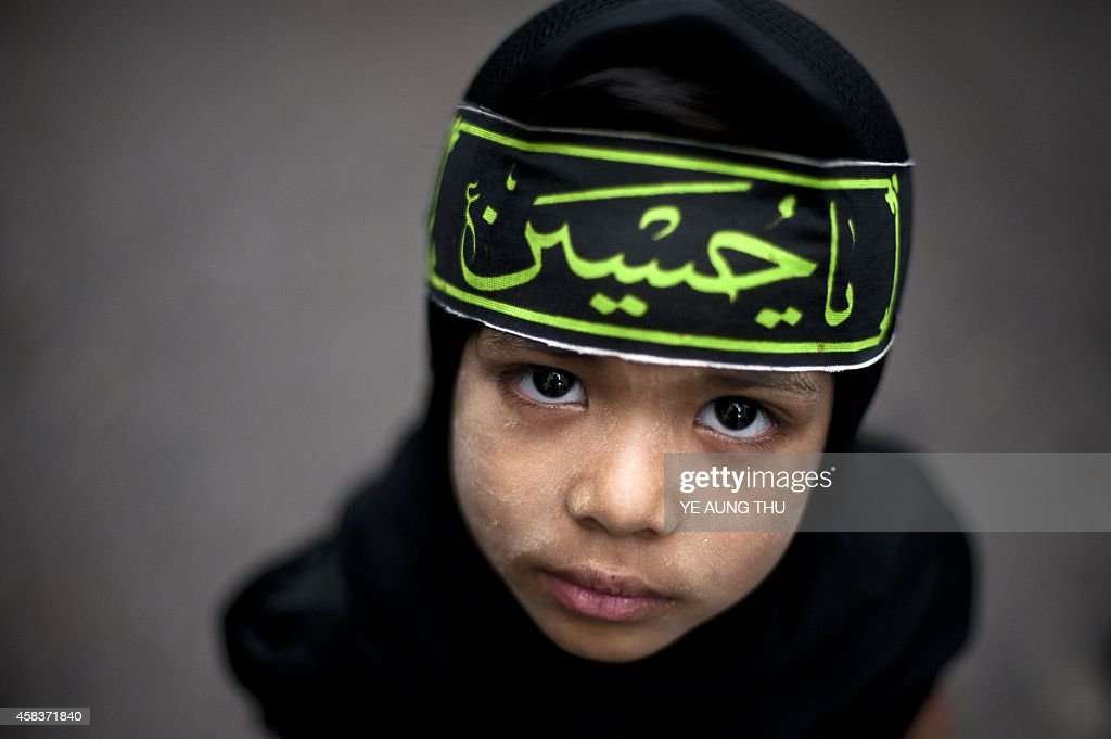 A Myanmar Shiite Muslim child looks up while outside a mosque during a procession to mark the Ashura festival in Yangon on November 4 2014 Ashura...