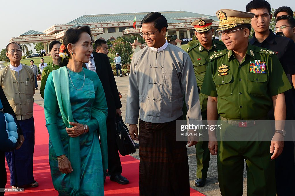 Myanmar State Counsellor and Foreign Minister Aung San Suu Kyi (L) and President Htin Kyaw (not in picture) are sent off by military chief Senior General Min Aung Hlaing (R) for an official trip to Laos from the Naypyidaw city airport on May 6, 2016. The official mission is their first foreign trip after being sworn into office on March 30. / AFP / AUNG
