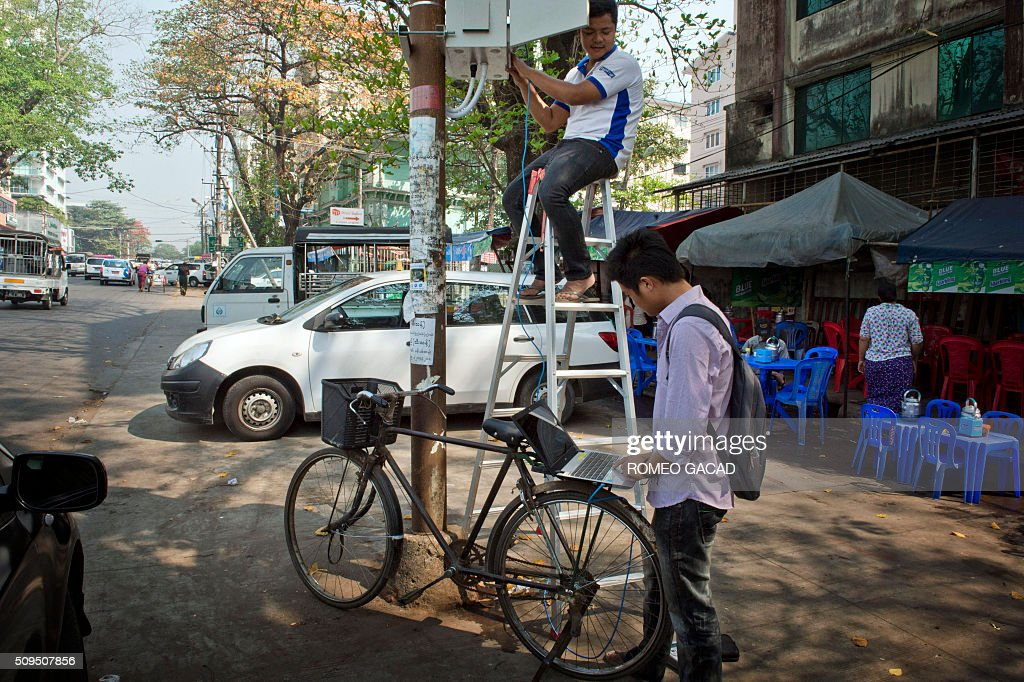 Myanmar telecom workers install Internet cable along a street in Yangon on February 11, 2016. Myanmar Internet users are benefiting from changes in the telecommunications law that encourages foreign direct investment in communications infrastructures, according to recent reports. AFP PHOTO / ROMEO GACAD / AFP / ROMEO GACAD