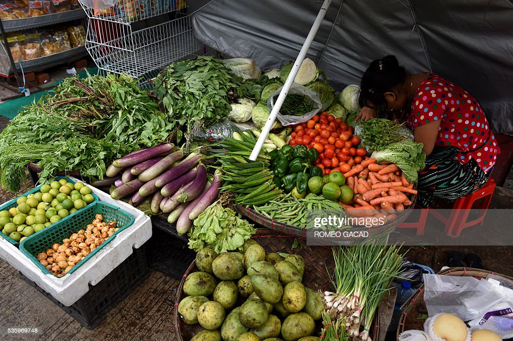 A Myanmar vegetable vendor rests at a sidewalk market in Yangon on May 31, 2016. Myanmar's growth rate, once one of the world's most impressive, has dipped following heavy floods and an investment slowdown sparked by uncertainty over its political transition, the World Bank said on May 31. / AFP / ROMEO