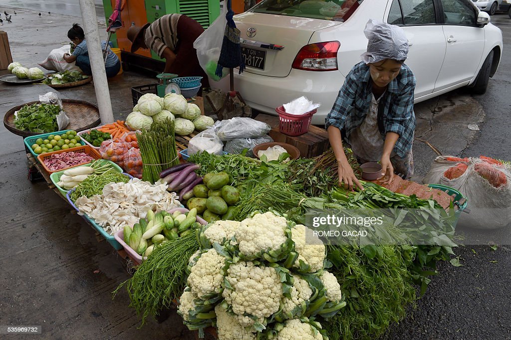 A Myanmar vegetable vendor tends to her sidewalk stall in Yangon on May 31, 2016. Myanmar's growth rate, once one of the world's most impressive, has dipped following heavy floods and an investment slowdown sparked by uncertainty over its political transition, the World Bank said on May 31. / AFP / ROMEO