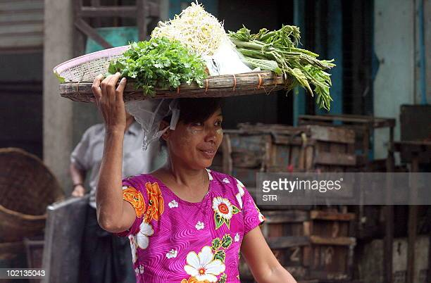 A Myanmar vegetables vendor makes her way through a street market in Lanmadaw township downtown Yangon on June 15 2010 Myanmar faces a tough task to...