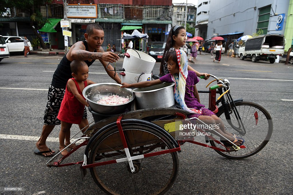 A Myanmar vendor accompanied by children transport pots of food by trishaw in Yangon on May 31, 2016. Myanmar's growth rate, once one of the world's most impressive, has dipped following heavy floods and an investment slowdown sparked by uncertainty over its political transition, the World Bank said on May 31. / AFP / ROMEO