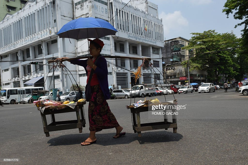 A Myanmar vendor walks with an umbrella in Yangon on April 28, 2016 amid rising summer temperature. The Meteorology and Hydrology Department has predicted that Myanmar will experience drought and record high temperatures following the effects of El Ni��o in March, April and May. / AFP / ROMEO