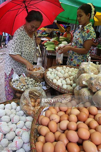 A Myanmar woman buys eggs at a street market in Lanmadaw township downtown Yangon on June 15 2010 Myanmar faces a tough task to eradicate extreme...