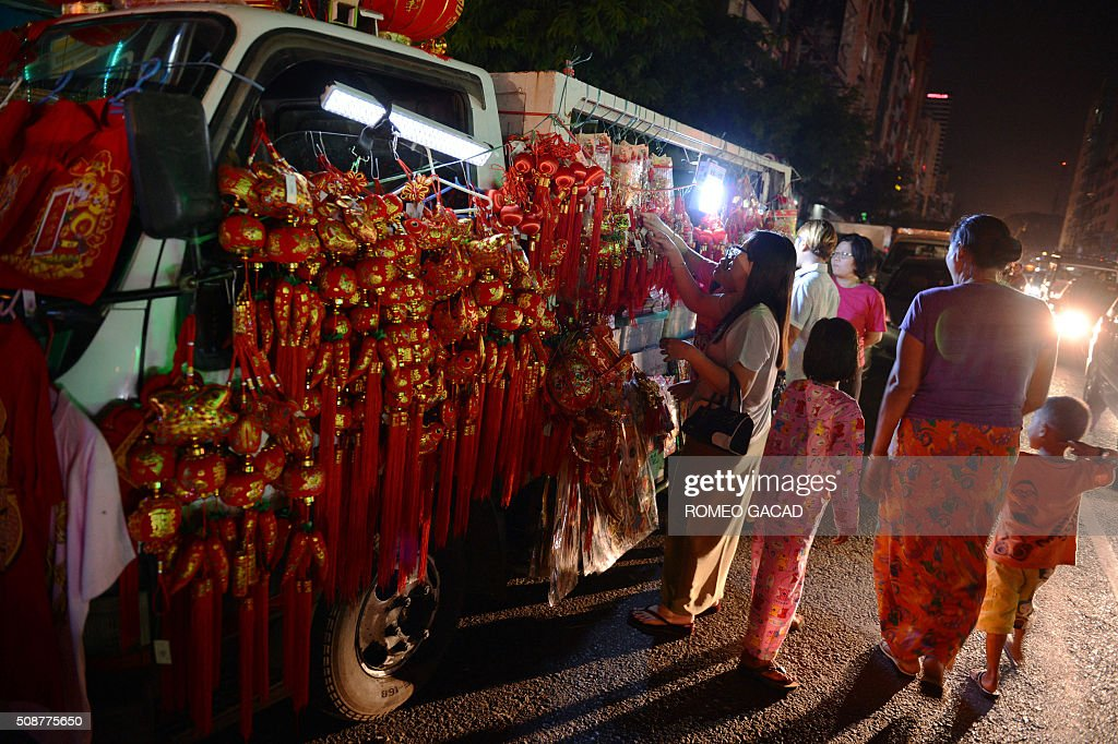 Myanmar women buy Chinese decorations during last minute rush in Yangon's Chinatown district on February 6, 2016 in preparation for the Lunar New Year celebrations which falls on February 8 and will mark the start of the year of the monkey. / AFP / ROMEO GACAD