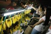 Myanmar women buy fruit from a street vendor in Yangon on March 8 2010 AFP PHOTO