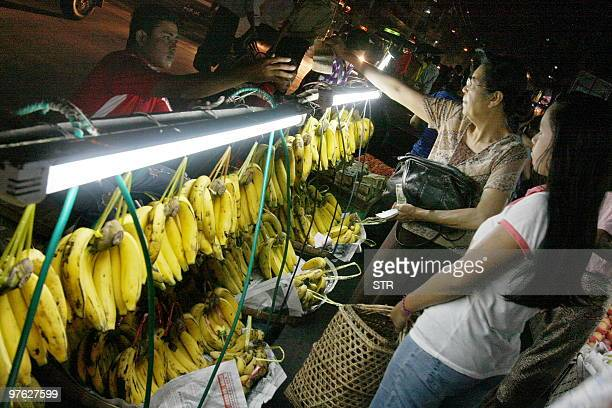 Myanmar women buy fruit from a street vendor in Yangon on March 8 2010 AFP PHOTO