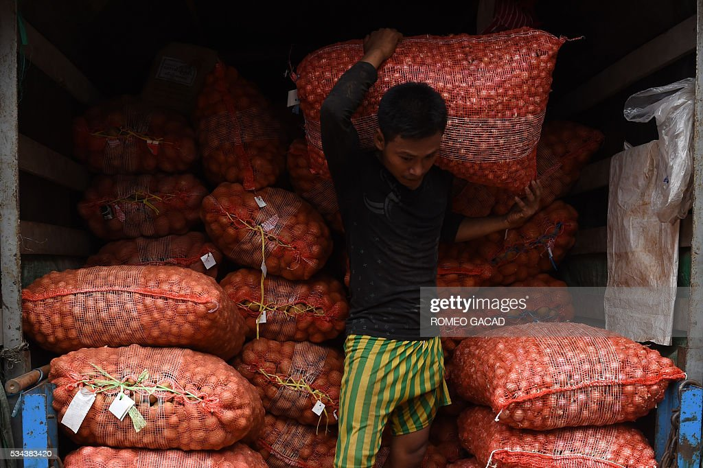 A Myanmar worker unloads sacks of potatoes at a market in Yangon on May 26, 2016. In the Asian Development Bank (ADB) Asian Outlook 2016 released in March 2016, the bank's prediction for the economy is to grow around 8.4 percent this fiscal year. / AFP / ROMEO