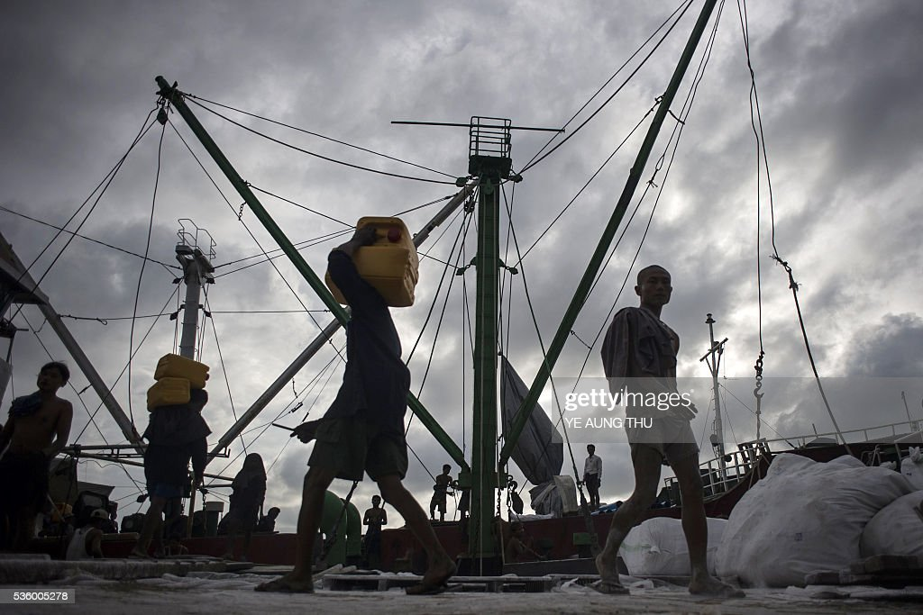 Myanmar workers load containers of oil onto a ship at the Yangon jetty on May 31, 2016. Myanmar's growth rate, once one of the world's most impressive, has dipped following heavy floods and an investment slowdown sparked by uncertainty over its political transition, the World Bank said on May 31. / AFP / YE
