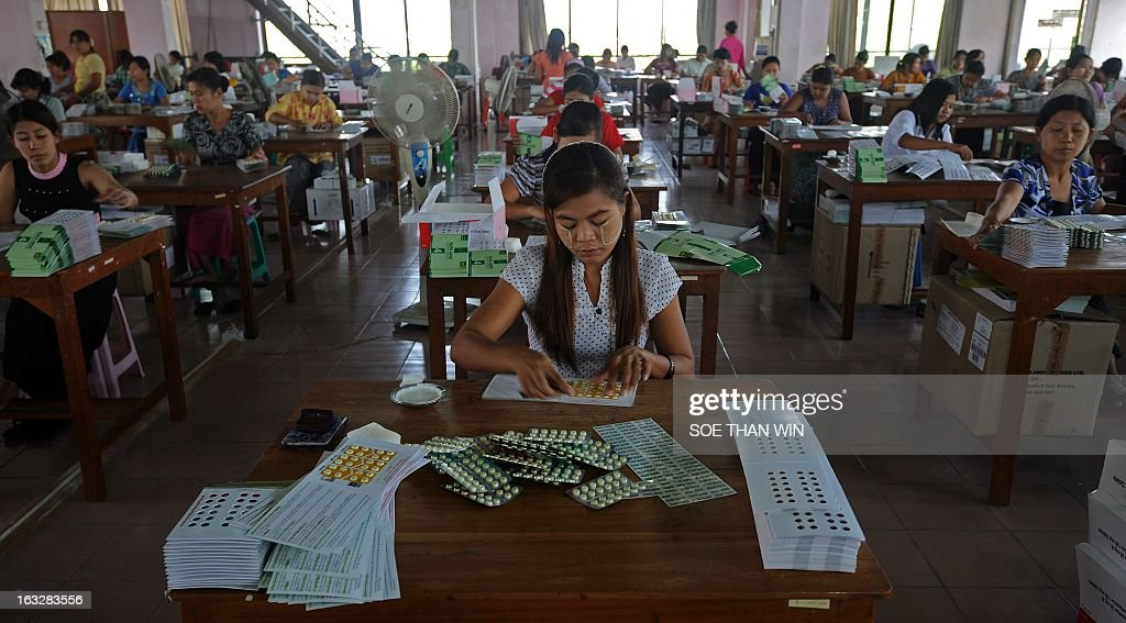 Myanmar workers pack medicine pills delivered into the country by the United States Agency for International Development (USAID) at a warehouse in Yangon on March 7, 2013. USAID administrator Rajiv Shah is on an official visit to Myanmar. AFP PHOTO/ Soe Than WIN