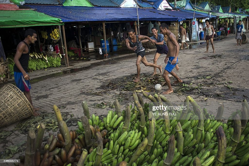 Myanmar workers play football at a banana market in Yangon on May 31, 2016. Myanmar's growth rate, once one of the world's most impressive, has dipped following heavy floods and an investment slowdown sparked by uncertainty over its political transition, the World Bank said on May 31. / AFP / YE
