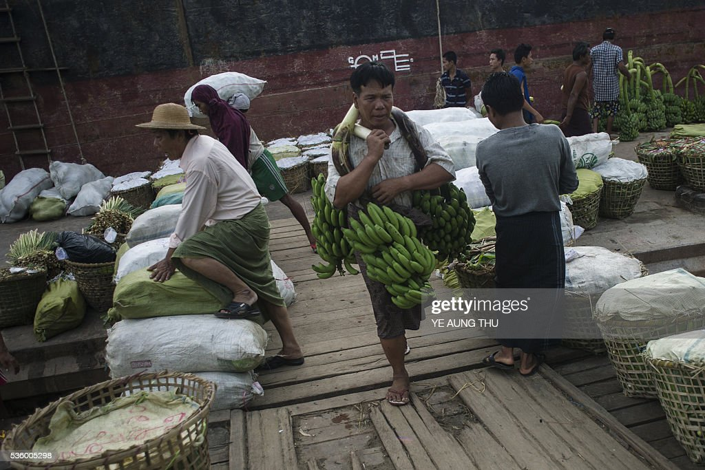 Myanmar workers unload bananas from a boat at a market in Yangon on May 31, 2016. Myanmar's growth rate, once one of the world's most impressive, has dipped following heavy floods and an investment slowdown sparked by uncertainty over its political transition, the World Bank said on May 31. / AFP / YE