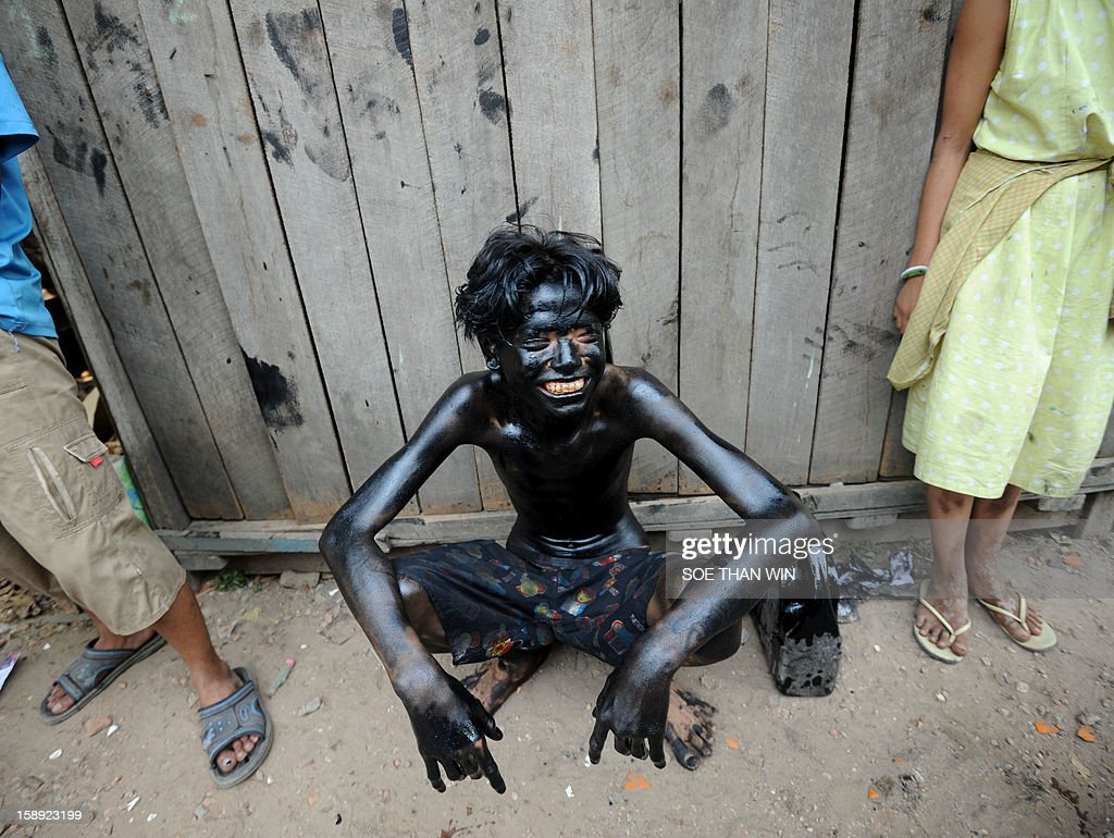 A Myanmar youngster (C) smeared with used car oil rests during a ball game using a coconut as part of celebrations to the 65th anniversary of Myanmar's independence, in Yangon on January 4, 2013. Myanmar, formerly known as Burma, gained independence from Britain on January 4, 1948. AFP PHOTO / Soe Than WIN