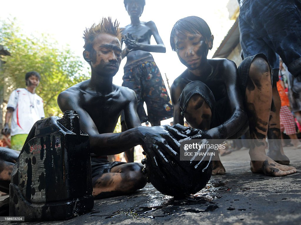 Myanmar youngsters apply used car engine oil on a cocunut as they play a game as they celebrate the 65th anniversary of Myanmar's independence, in Yangon on January 4, 2013. Myanmar, formerly known as Burma, gained independence from Britain on January 4, 1948. AFP PHOTO / Soe Than WIN