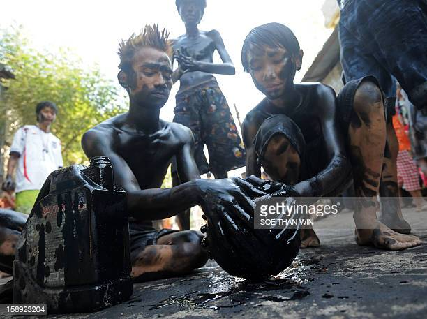 Myanmar youngsters apply used car engine oil on a cocunut as they play a game as they celebrate the 65th anniversary of Myanmar's independence in...
