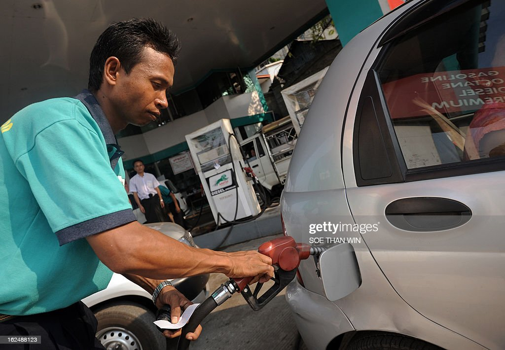 Myanmar-economy-oil-gas, FOCUS by Shwe Yinn Mar Oo This picture taken on February 23, 2013, shows a Myanmar worker filling up a car at a petrol station in Yangon. While other countries may be more reliable and better equipped, Myanmar has emerged as the new promised land for global oil and gas giants unperturbed by a lack of data on its proven energy reserves. AFP PHOTO/ Soe Than WIN