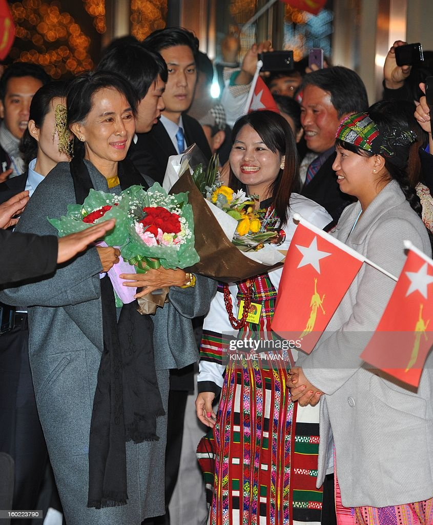 Myanmarese living in South Korea greet Myanmar's opposition leader Aung San Suu Kyi upon her arrival at at hotel in Seoul on January 28, 2013. Suu Kyi arrived in South Korea for a four-day visit including meetings with politicians and a soap-opera star and the collection of a human rights award.