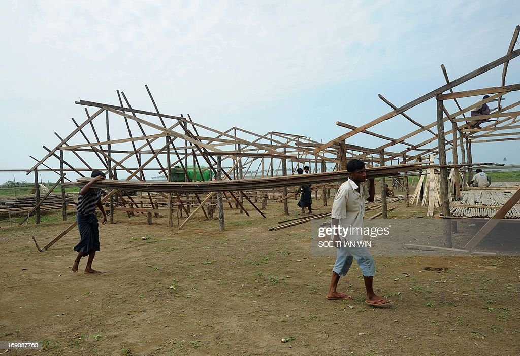 Myanmar-religion-unrest-rights, FOCUS by Shwe Yinn Mar Oo Rohingya men construct new barracks at Bawdupah's Internally Displaced People (IDP) camp on the outskirts of Sittwe on May 18, 2013. Myanmar's victims of sectarian strife were spared the full force of Cyclone Mahasen, but many are now returning to flimsy tents in flood-prone camps with the monsoon just weeks away. AFP PHOTO / Soe Than WIN
