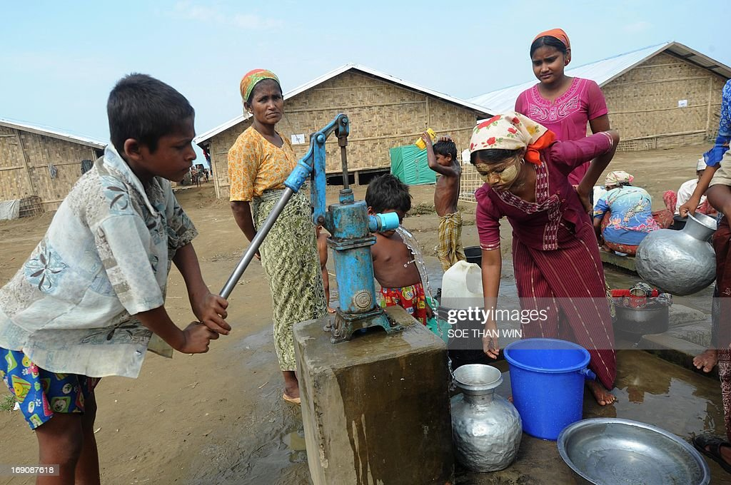 Myanmar-religion-unrest-rights, FOCUS by Shwe Yinn Mar Oo Rohingya people collect water from a well near their barracks at Bawdupah's Internally Displaced People (IDP) camp on the outskirts of Sittwe on May 18, 2013. Myanmar's victims of sectarian strife were spared the full force of Cyclone Mahasen, but many are now returning to flimsy tents in flood-prone camps with the monsoon just weeks away. AFP PHOTO / Soe Than WIN