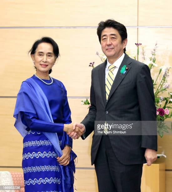 Myanmar's democratic leader Aung San Suu Kyi and Japanese Prime Minister Shinzo Abe shake hands during their meeting at Abe's official residence on...