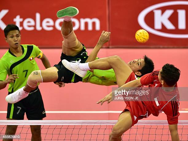 Myanmar's Latt Zaw strikes the ball against Indonesia's Nofrizal in the men's double preliminary group B sepaktakraw match during the 2014 Asian...