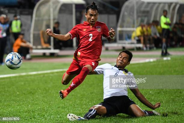 Myanmar's Nan Wai Min fights for the ball with Laos' Sonthanalay Khampanh during their men's football Group A round match at the 29th Southeast Asian...