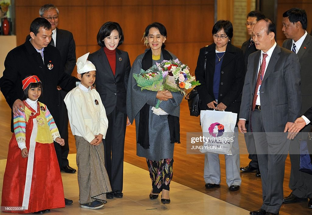 Myanmar's opposition leader Aung San Suu Kyi (C) arrives at Incheon international airport, west of Seoul, on January 28, 2013. Suu Kyi arrived in South Korea for a four-day visit including meetings with politicians and a soap-opera star and the collection of a human rights award.