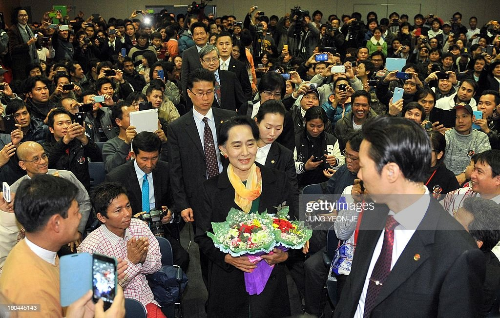 Myanmar's opposition leader Aung San Suu Kyi (C) arrives to attend a meeting with Myanmar people living in South Korea in Seoul on February 1, 2013. Suu Kyi arrived in South Korea on January 28 for a four-day visit including meetings with politicians and a soap-opera star and the collection of a human rights award.