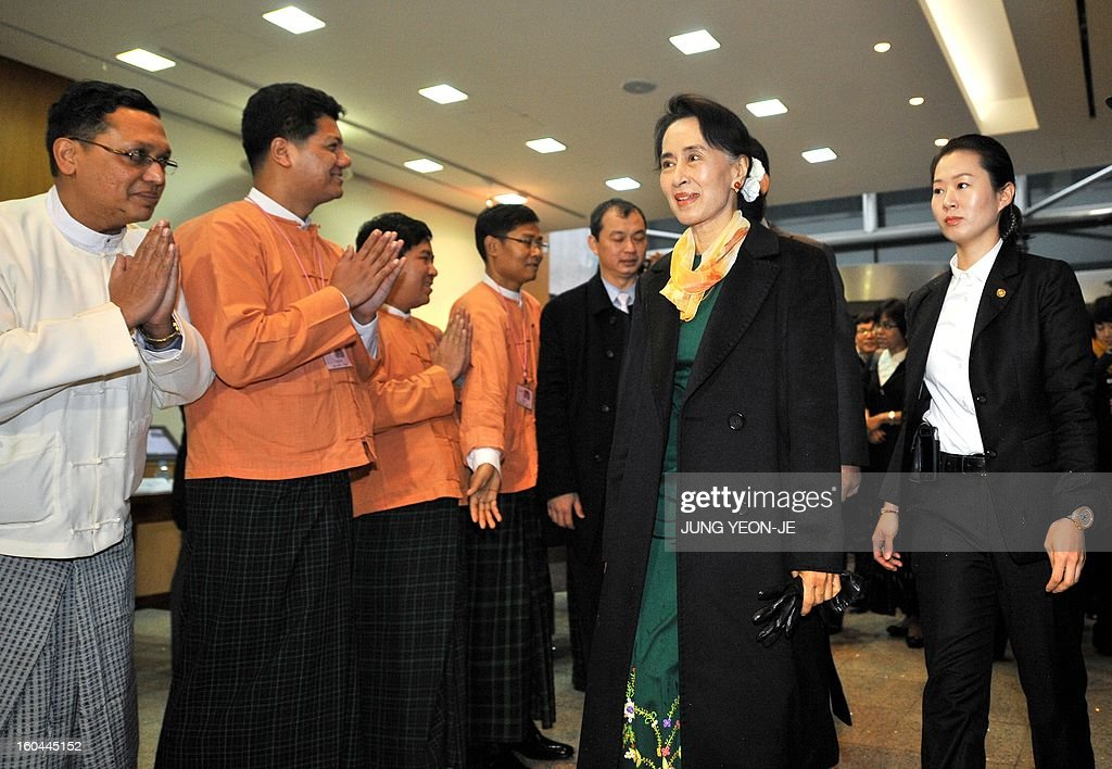 Myanmar's opposition leader Aung San Suu Kyi (2nd R) arrives to attend a meeting with Myanmar people living in South Korea in Seoul on February 1, 2013. Suu Kyi arrived in South Korea on January 28 for a four-day visit including meetings with politicians and a soap-opera star and the collection of a human rights award.
