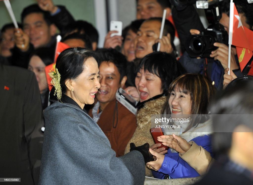 Myanmar's opposition leader Aung San Suu Kyi (L front) greets Myanmarese living in South Korea upon her arrival at Incheon international airport, west of Seoul, on January 28, 2013. Suu Kyi arrived in South Korea for a four-day visit including meetings with politicians and a soap-opera star and the collection of a human rights award. AFP PHOTO / JUNG YEON-JE