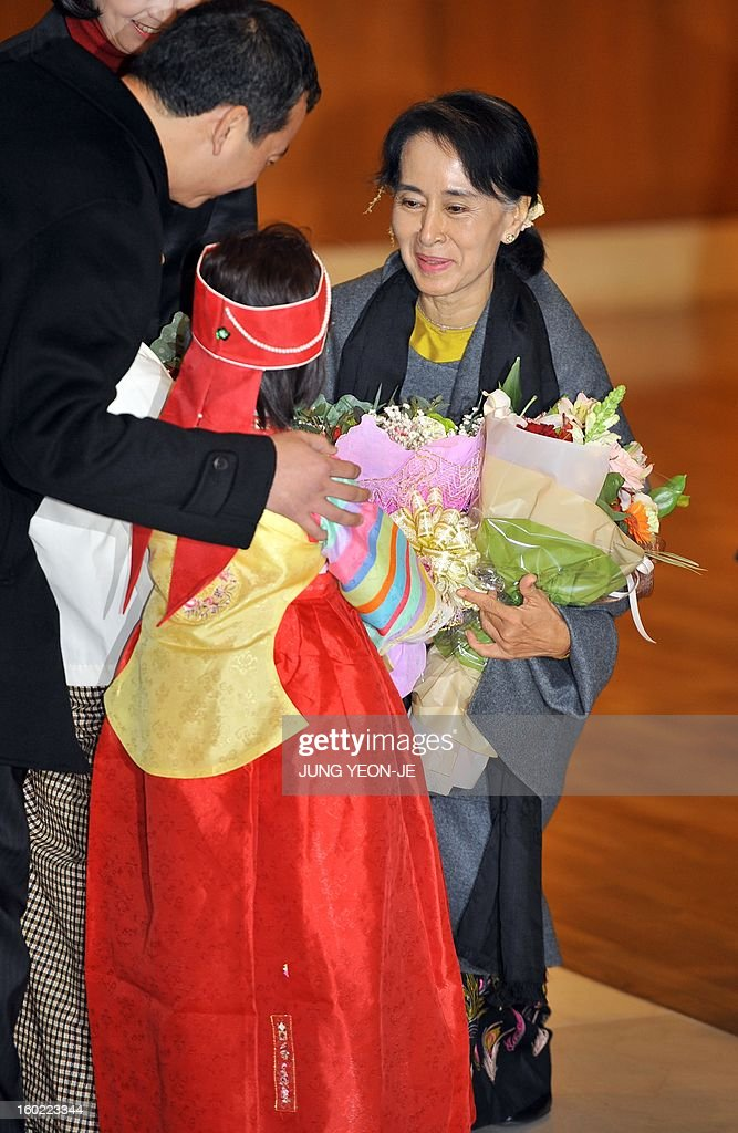 Myanmar's opposition leader Aung San Suu Kyi (R) receives flowers from a Myanmarese girl (C) wearing a traditional Korean dress upon her arrival at Incheon international airport, west of Seoul, on January 28, 2013. Suu Kyi arrived in South Korea for a four-day visit including meetings with politicians and a soap-opera star and the collection of a human rights award.