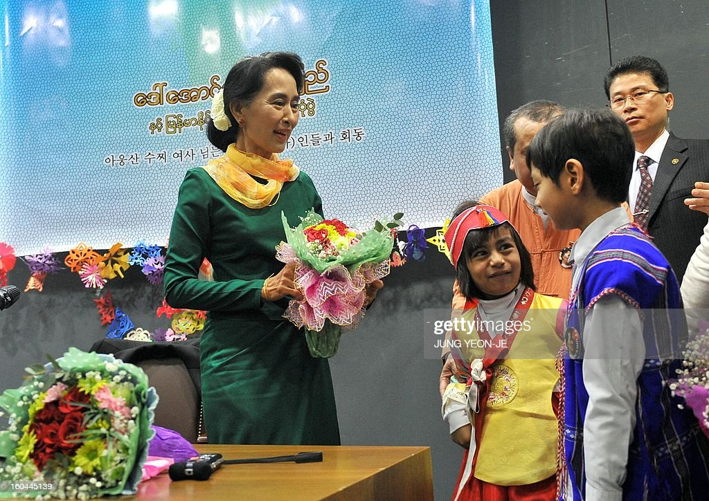 Myanmar's opposition leader Aung San Suu Kyi (L) receives flowers from Myanmarese children during a meeting with Myanmar people living in South Korea in Seoul on February 1, 2013. Suu Kyi arrived in South Korea on January 28 for a four-day visit including meetings with politicians and a soap-opera star and the collection of a human rights award.