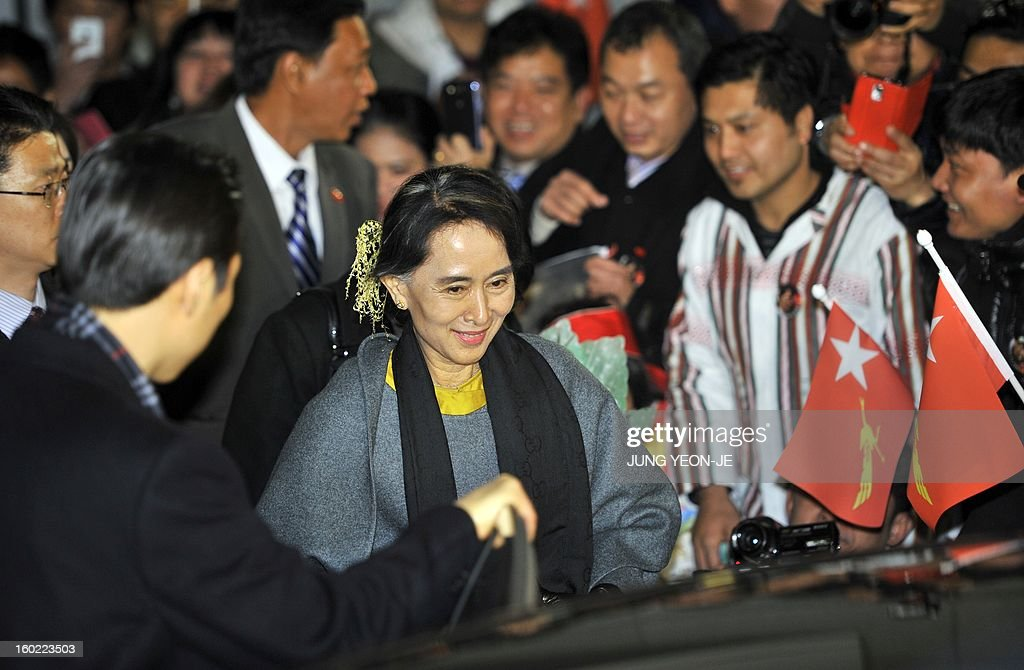 Myanmar's opposition leader Aung San Suu Kyi (C) rides in a car after she greeted Myanmarese living in South Korea upon her arrival at Incheon international airport, west of Seoul, on January 28, 2013. Suu Kyi arrived in South Korea for a four-day visit including meetings with politicians and a soap-opera star and the collection of a human rights award. AFP PHOTO / JUNG YEON-JE