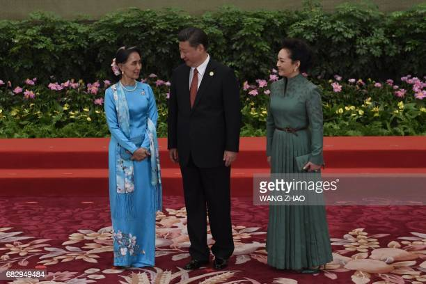Myanmar's State Counsellor Aung San Suu Kyi talks with Chinese President Xi Jinping and his wife Peng Liyuan during a welcome ceremony for leaders...