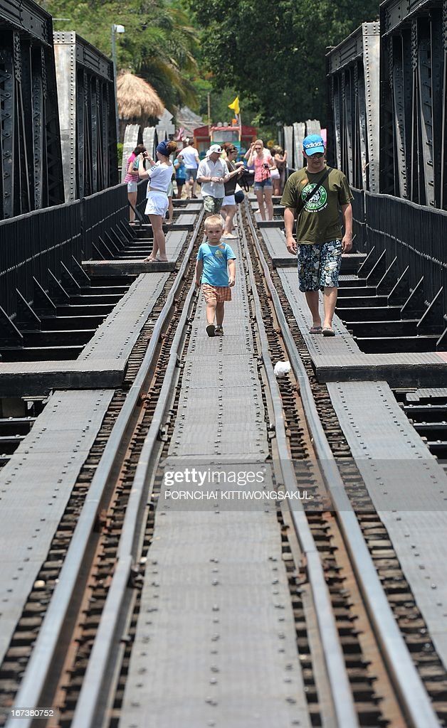 WITH 'Myanmar-Thailand-Japan-WWII-history-rail-tourism' FEATURE by Kelly Macnamara In a picture taken on April 24, 2013, foreign tourists walk on a railway bridge over the river Kwai build during World War II in Kanchanaburi province. An elegant cemetery in strife-torn southeast Myanmar has long stood as a lonely testament to the fate of thousands of prisoners of war who died building Japan's 'Death Railway'.