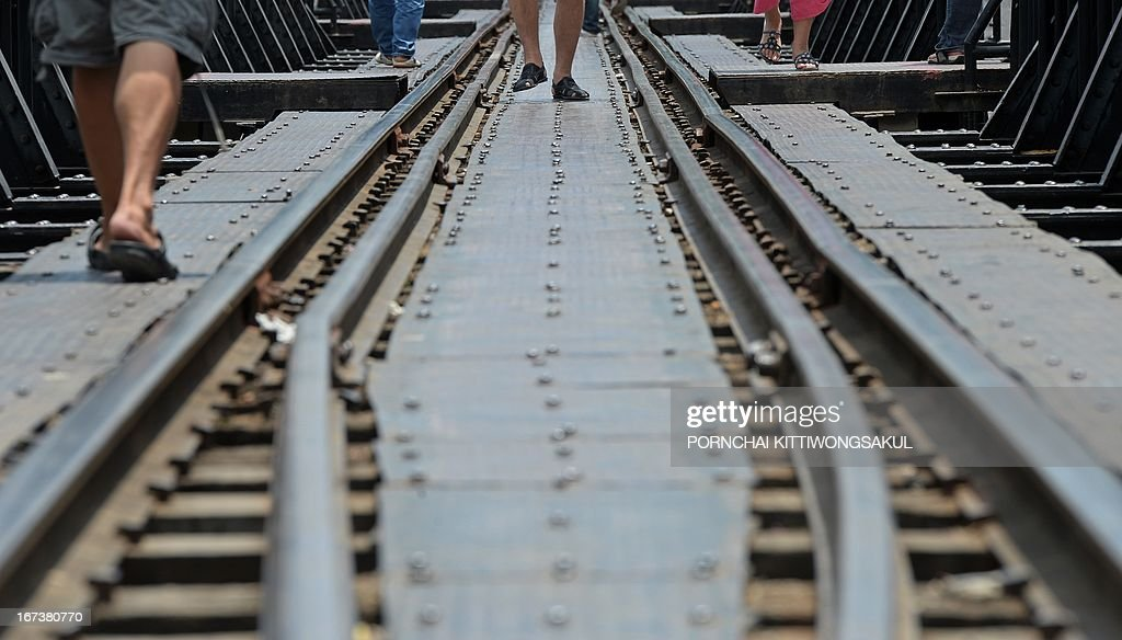 WITH 'Myanmar-Thailand-Japan-WWII-history-rail-tourism' FEATURE by Kelly Macnamara In a picture taken on April 24, 2013, tourists walk on a railway bridge over the river Kwai build during World War II in Kanchanaburi province. An elegant cemetery in strife-torn southeast Myanmar has long stood as a lonely testament to the fate of thousands of prisoners of war who died building Japan's 'Death Railway'.