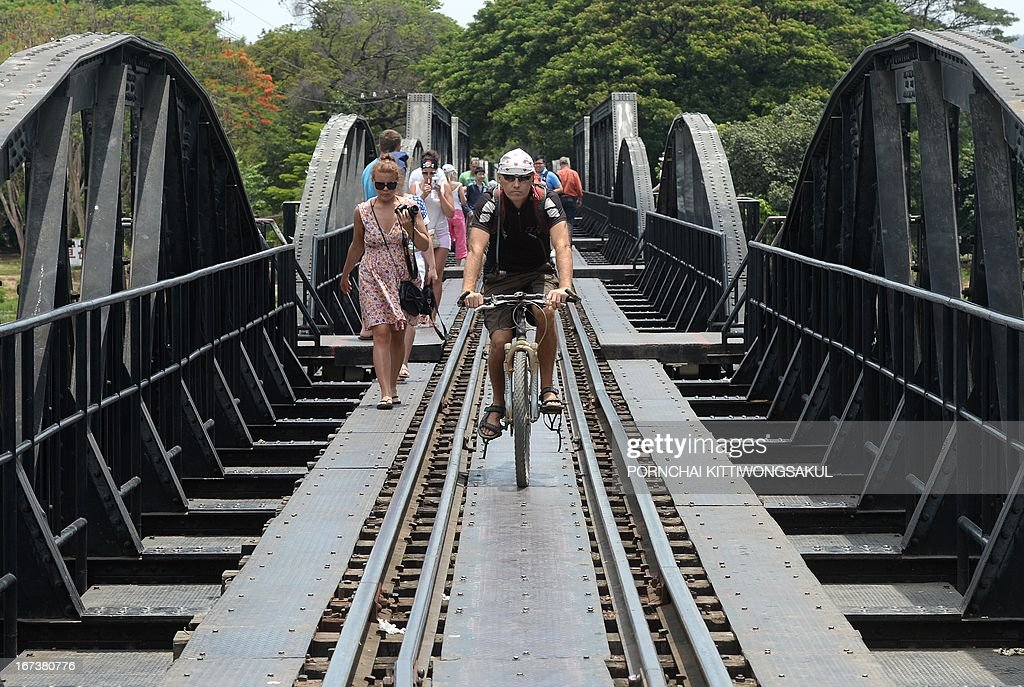 WITH 'Myanmar-Thailand-Japan-WWII-history-rail-tourism' FEATURE by Kelly Macnamara In a picture taken on April 24, 2013, foreign tourists walk on a railway bridge over the river Kwai build during World War II in Kanchanaburi province. An elegant cemetery in strife-torn southeast Myanmar has long stood as a lonely testament to the fate of thousands of prisoners of war who died building Japan's 'Death Railway'. AFP PHOTO / PORNCHAI KITTIWONGSAKUL