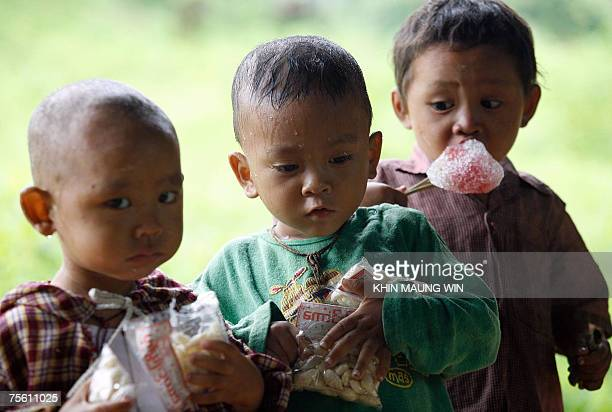 Myanmese children eat snacks at a rice field in Yangon 15 July 2007 The US House of Representatives voted 23 July 2007 to renew a ban on all imports...