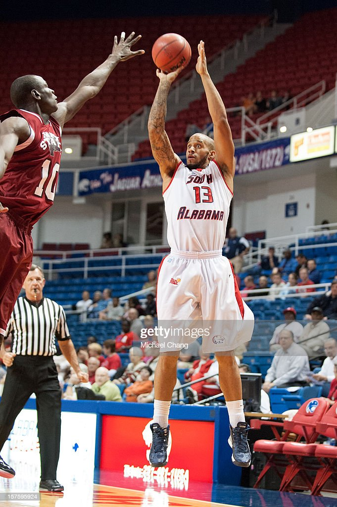 Mychal Ammons #13 of the South Alabama Jaguars takes a shot over Bandja Sy #10 of the New Mexico State Aggies at USA Mitchell Center on December 4, 2012 in Mobile, Alabama. At halftime New Mexico State leads South Alabama 31-25.