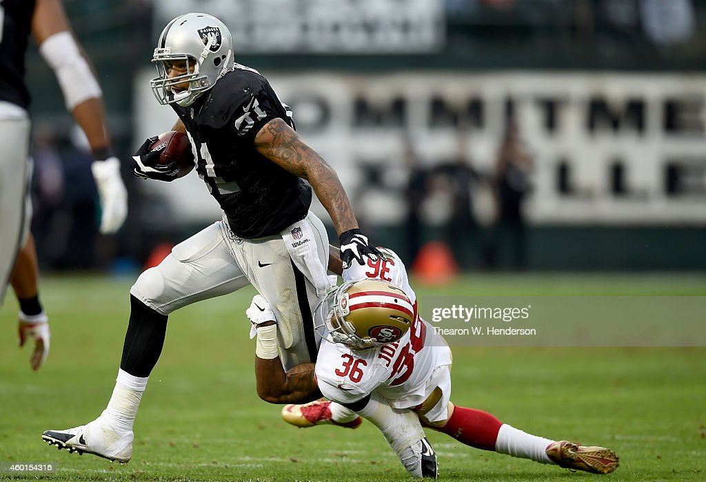 <a gi-track='captionPersonalityLinkClicked' href=/galleries/search?phrase=Mychal+Rivera&family=editorial&specificpeople=8281492 ng-click='$event.stopPropagation()'>Mychal Rivera</a> #81 of the Oakland Raiders gets tackled by <a gi-track='captionPersonalityLinkClicked' href=/galleries/search?phrase=Dontae+Johnson&family=editorial&specificpeople=7199526 ng-click='$event.stopPropagation()'>Dontae Johnson</a> #36 of the San Francisco 49ers in the third quarter at O.co Coliseum on December 7, 2014 in Oakland, California.