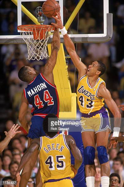 Mychal Thompson of the Los Angeles Lakers battles for a rebound with Rick Mahorn of the Detroit Pistons during an NBA game at the Great Western Forum...